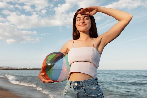 Średnio strzał uśmiechnięta kobieta trzymająca piłkę