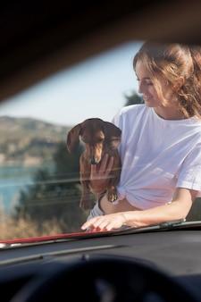 Średnio strzał uśmiechnięta kobieta trzymająca psa