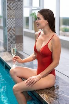 Średnio strzał uśmiechnięta kobieta trzymająca szklankę