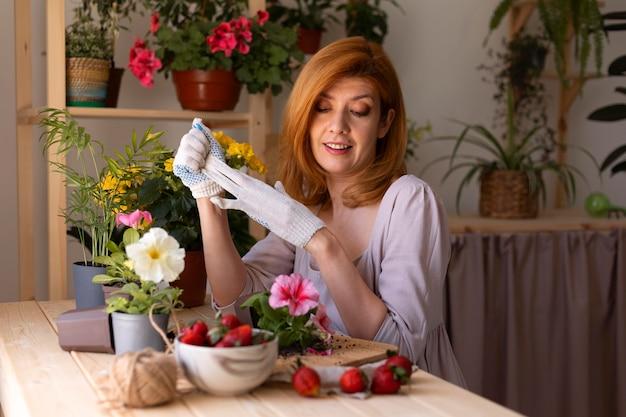 Średnio strzał uśmiechnięta kobieta z kwiatami