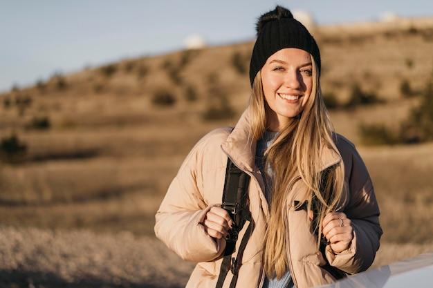 Średnio strzał uśmiechnięta kobieta z plecakiem