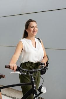 Średnio strzał uśmiechnięta kobieta z rowerem