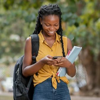 Średnio strzał uśmiechnięta kobieta z smartphone