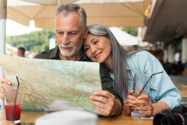 Średnio strzał uśmiechnięta para trzymająca mapę