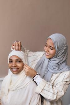 Średnio strzał uśmiechnięte kobiety noszące hidżab