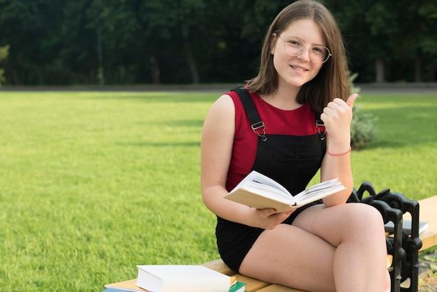 Średnio strzał uśmiechniętej dziewczyny highschool siedzi
