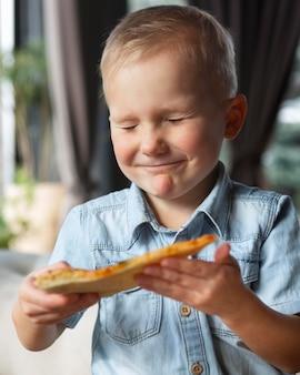 Średnio strzał uśmiechnięty dzieciak z kawałkiem pizzy