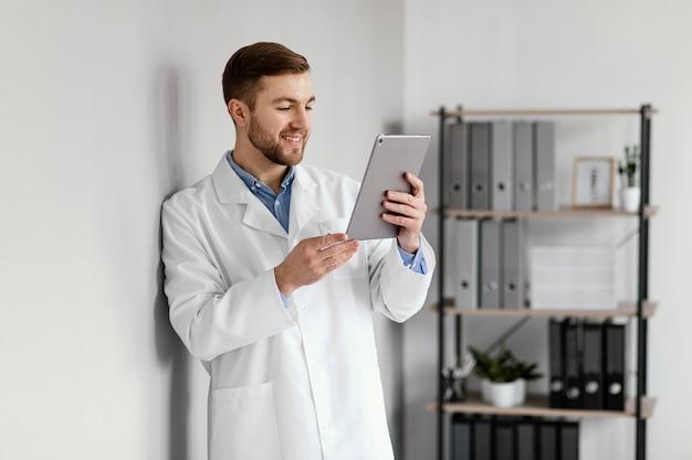 Średnio strzał uśmiechnięty lekarz trzymając tabletkę