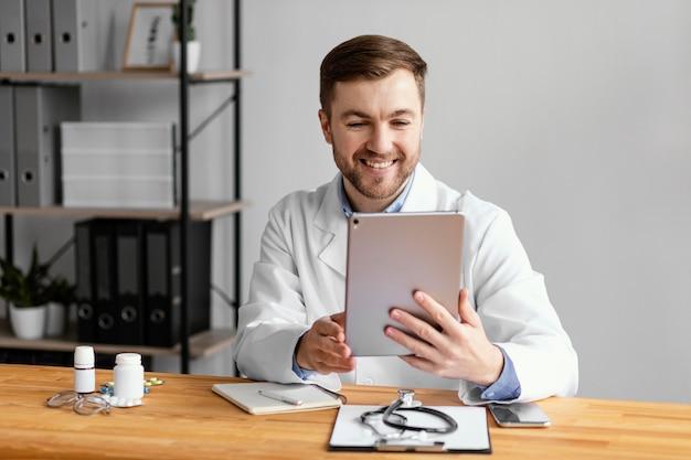 Średnio Strzał Uśmiechnięty Lekarz Trzymając Tabletkę Premium Zdjęcia