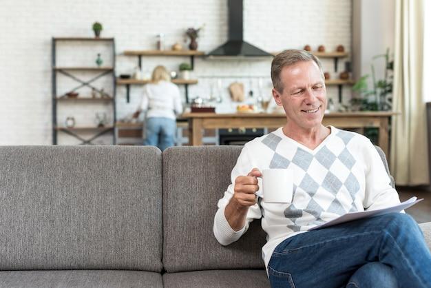 Średnio strzał uśmiechnięty mężczyzna czyta na kanapie