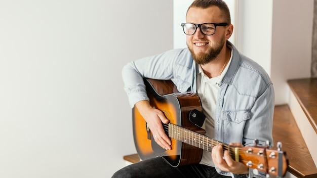 Średnio strzał uśmiechnięty mężczyzna gra na gitarze