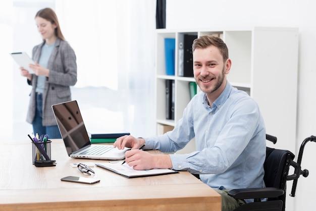 Średnio strzał uśmiechnięty mężczyzna pracujący w pomieszczeniu
