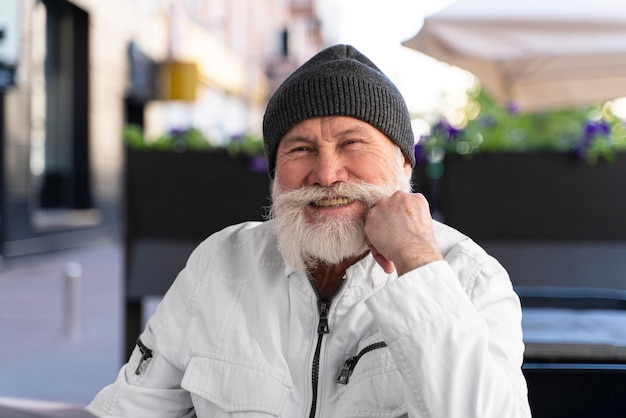 Średnio strzał uśmiechnięty mężczyzna siedzący na tarasie