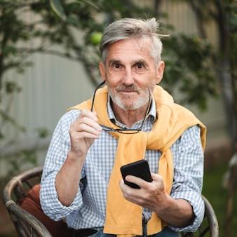 Średnio strzał uśmiechnięty mężczyzna trzyma smartfon