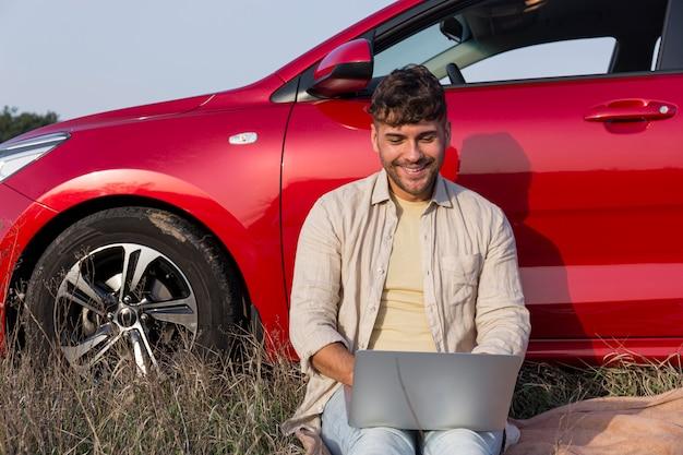 Średnio strzał uśmiechnięty mężczyzna z laptopem