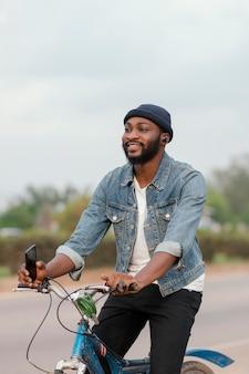 Średnio strzał uśmiechnięty mężczyzna z rowerem