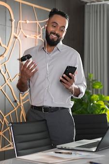 Średnio strzał uśmiechnięty mężczyzna ze smartfonem