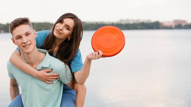 Średnio strzał uśmiechniętych przyjaciół z frisbee na zewnątrz