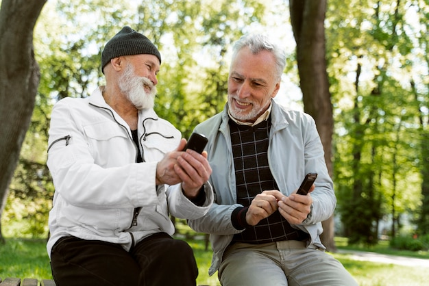 Średnio strzał uśmiechniętych starców ze smartfonami
