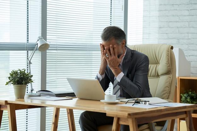 Średnio strzał z biznesmenem siedzącym przy biurku z rękami na twarzy sfrustrowanej niepowodzeniem