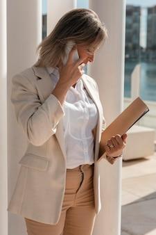 Średnio strzał zajęta kobieta rozmawiająca przez telefon