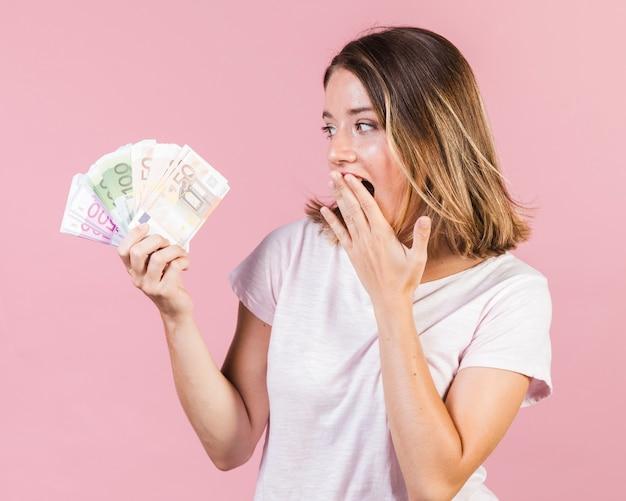 Średnio strzał zaskoczony dziewczyna trzyma pieniądze