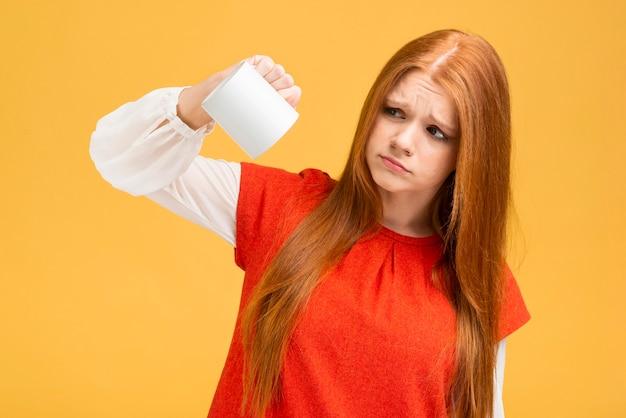 Średnio strzał zdenerwowany dziewczyna trzyma kubek