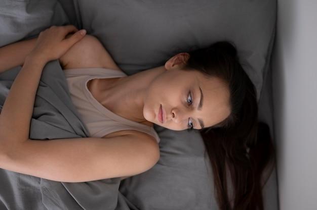 Średnio strzał zmęczona kobieta w łóżku