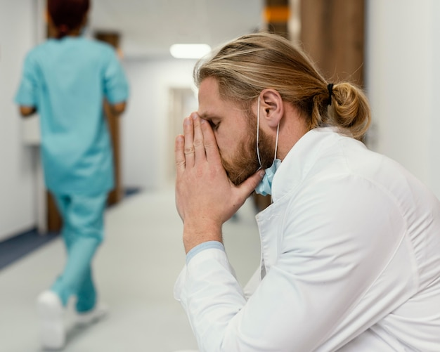 Średnio strzał zmęczony lekarz z maską