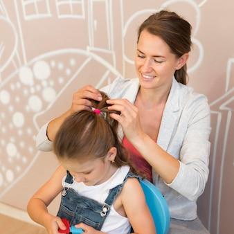 Średnio strzałowa buźka nauczycielka wiążąca włosy dziewczyny