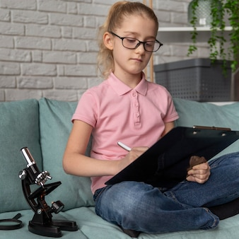 Średnio strzałowa dziewczyna robiąca notatki