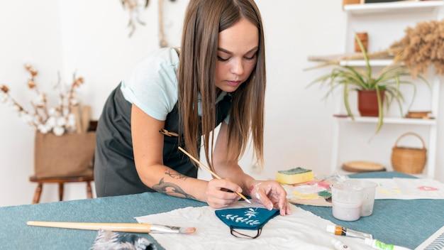 Średnio strzałowa kobieta malująca maskę