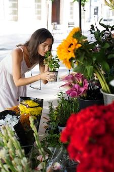 Średnio strzałowa kobieta pachnąca rośliną