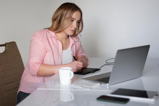 Średnio strzałowa kobieta pracująca w domu