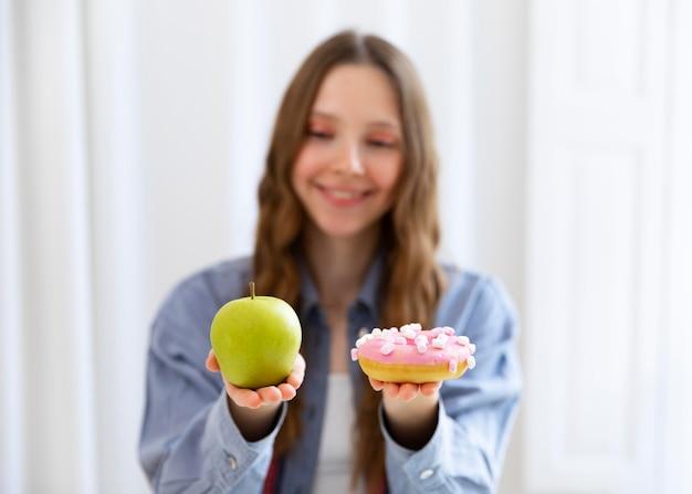 Średnio strzałowa kobieta z pączkiem i jabłkiem
