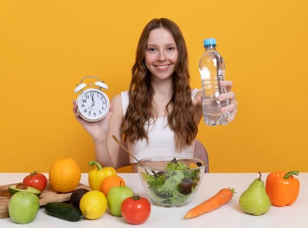 Średnio strzałowa kobieta z warzywami i wodą