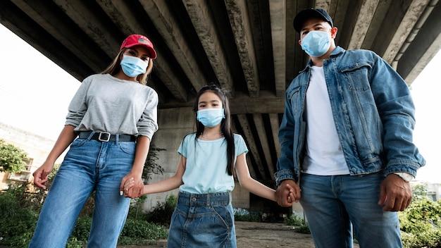 Średnio strzałowa rodzina nosząca maski na twarz