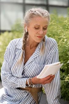 Średnio strzałowa starsza kobieta czytająca książkę