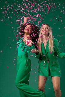 Średnio strzałowe kobiety pozujące z konfetti