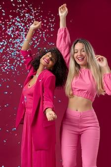 Średnio strzałowe kobiety tańczące z konfetti