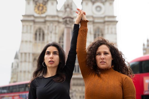 Średnio strzałowe kobiety trzymające się za ręce