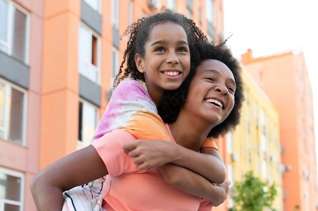 Średnio strzałowe uśmiechnięte dziewczyny bawią się