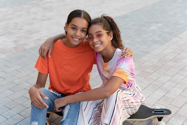 Średnio strzałowe uśmiechnięte dziewczyny na deskorolce
