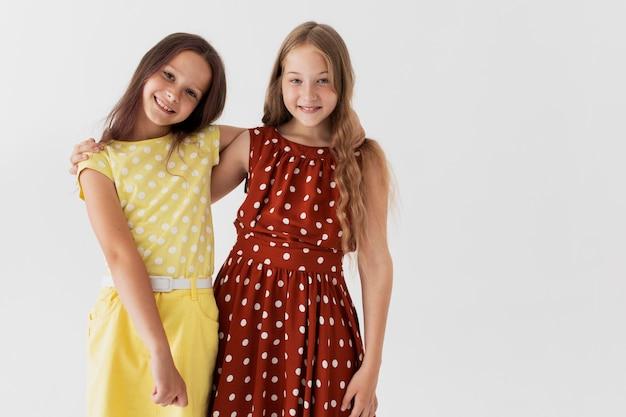 Średnio strzałowe uśmiechnięte dziewczyny pozują razem