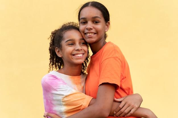 Średnio strzałowe uśmiechnięte dziewczyny przytulające się