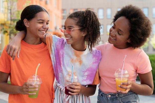 Średnio strzałowe uśmiechnięte dziewczyny trzymające napoje