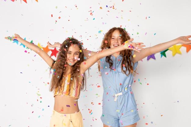 Średnio strzałowe uśmiechnięte dziewczyny z kolorowym konfetti