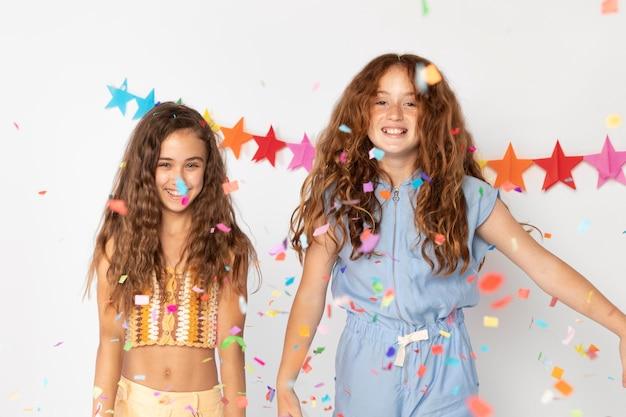 Średnio strzałowe uśmiechnięte dziewczyny z konfetti