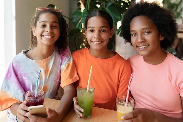 Średnio strzałowe uśmiechnięte dziewczyny z napojami