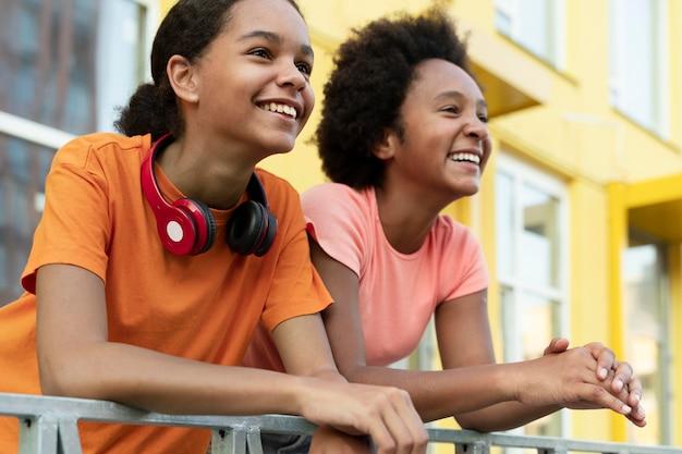 Średnio strzałowe uśmiechnięte dziewczyny ze słuchawkami